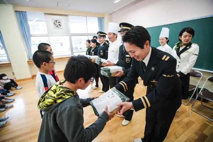 松江市立宍道小学校の児童に記念ノベルティーを贈る「瑞風」クルーたち